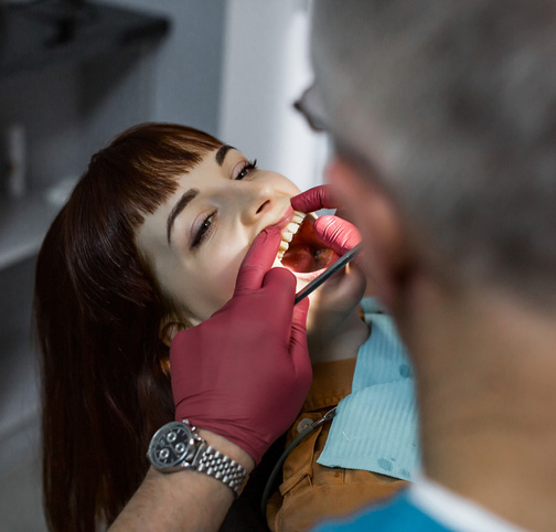 Young cheerful Caucasian woman during examination in dental clinic. Senior male doctor dentist doing dental oral check in modern clinic