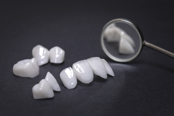 Dental mirror with zircon dentures on a dark background – Ceramic veneers – lumineers